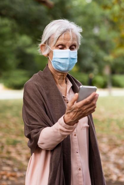 의료 마스크와 스마트 폰 세 여자의 전면보기 무료 사진