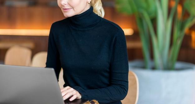 Вид спереди пожилой женщины, работающей на ноутбуке Бесплатные Фотографии