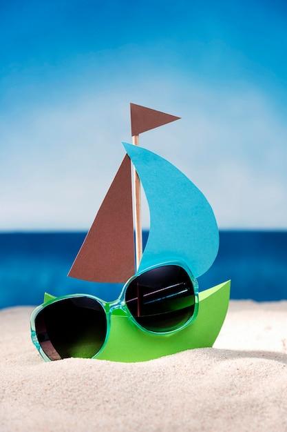サングラスとビーチの砂の上の紙の船の正面図 無料写真