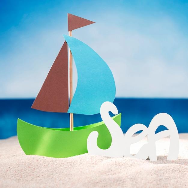 ビーチでの紙の船の正面図 無料写真