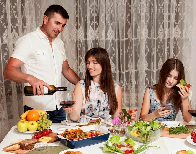 両親と夕食の席で娘の正面図 無料写真
