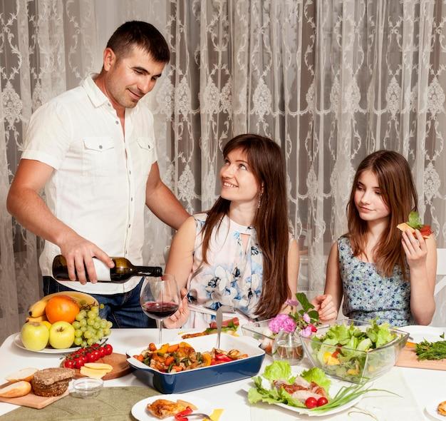 夕食の席でワインを持っている親の正面図 無料写真