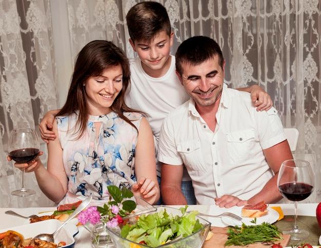 夕食の席で息子と両親の正面図 無料写真