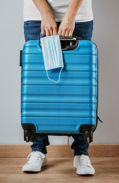 Вид спереди человека, держащего багаж и медицинскую маску Premium Фотографии