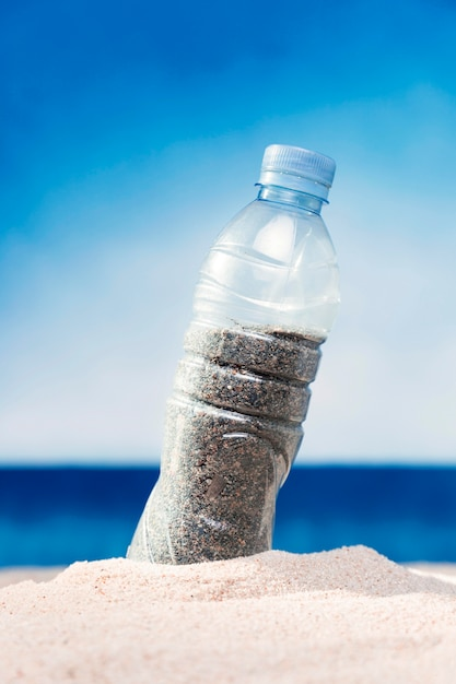 ビーチで砂で満たされたペットボトルの正面図 無料写真