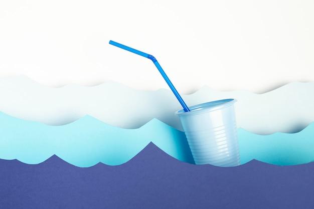 わらと紙の波とプラスチック製のコップの正面図 無料写真
