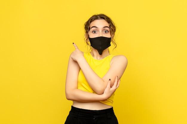 Вид спереди красивой женщины в черной маске на желтом Бесплатные Фотографии
