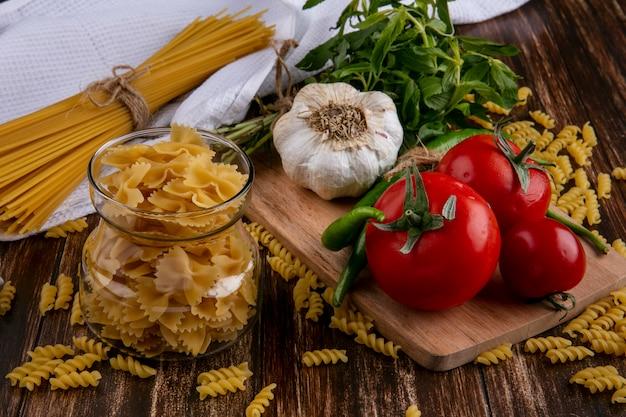 まな板の上のトマトニンニクと唐辛子の瓶にパスタと木製の表面にミントの束と生のスパゲッティの正面図 無料写真