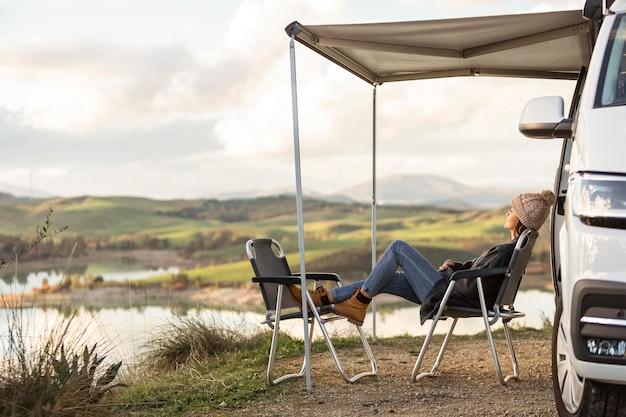 女性がリラックスして湖の横にあるロードトリップ車の正面図 無料写真
