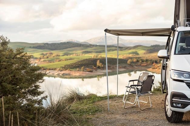 湖の横にあるロードトリップカーの正面図 無料写真