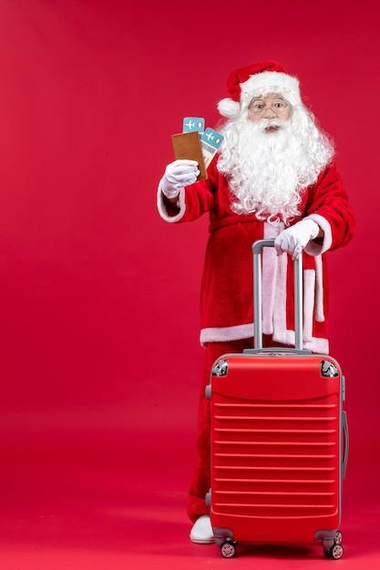 Вид спереди санта-клауса с сумкой, держащей билеты и готовящейся к поездке на красной стене Бесплатные Фотографии