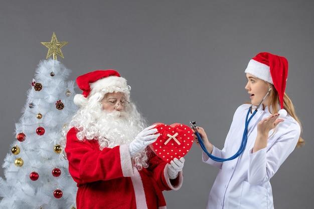 灰色の壁に聴診器でプレゼントを観察している女性医師とサンタクロースの正面図 無料写真