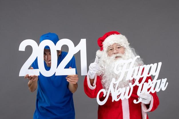 회색 벽에 남성 택배 지주와 새해 복 많이 받으세요 2021 보드와 산타 클로스의 전면보기 무료 사진