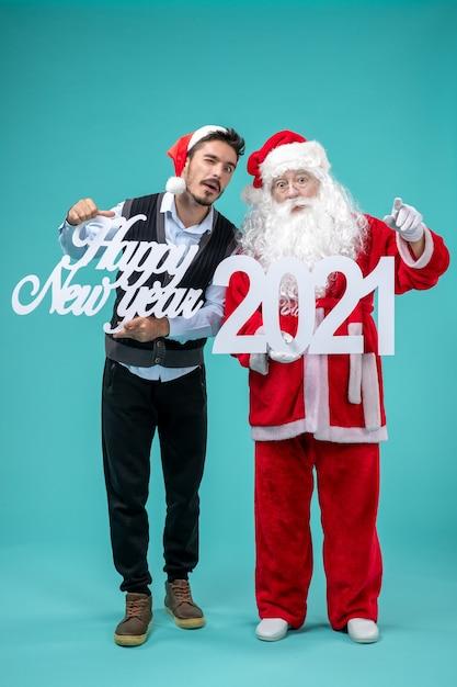 파란색 벽에 새해 복 많이 받으세요 및 2021 보드를 들고 남성과 산타 클로스의 전면보기 무료 사진