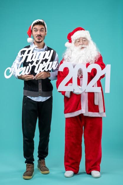 파란색 벽에 새 해 복과 2021 보드를 들고 남자와 산타 클로스의 전면보기 무료 사진