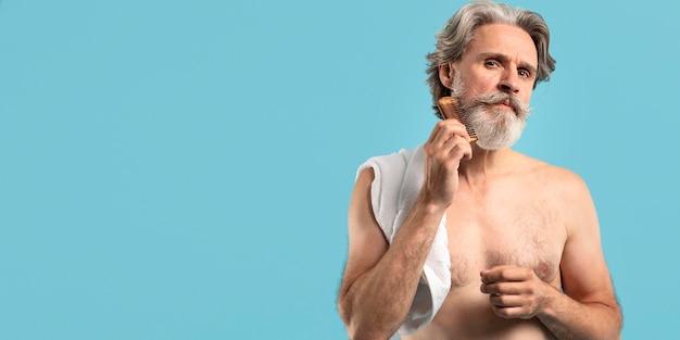 ひげをとかすシャワーの後のシニアの正面図 無料写真