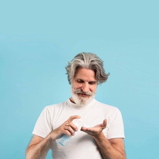 コピースペースで洗剤を使用している年配の男性人の正面図 無料写真