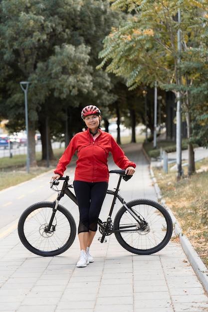Вид спереди пожилой женщины, позирующей на открытом воздухе с велосипедом Бесплатные Фотографии