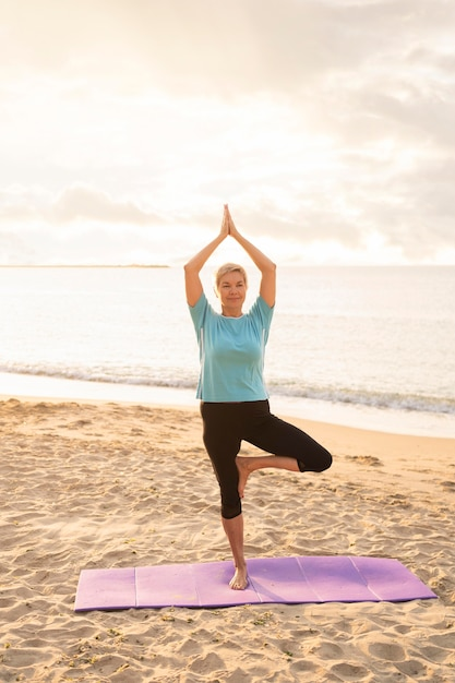 Вид спереди пожилой женщины, практикующей йогу на пляже Бесплатные Фотографии