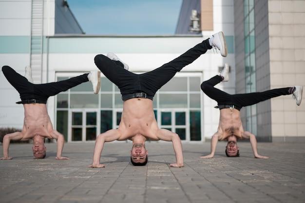 Вид спереди без рубашки хип-хоп артистов, танцующих на головах Бесплатные Фотографии