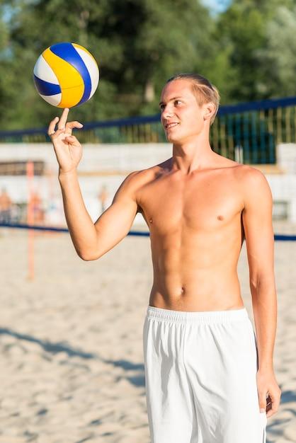 ビーチでボールを使ってトリックを行う上半身裸の男性のバレーボール選手の正面図 無料写真
