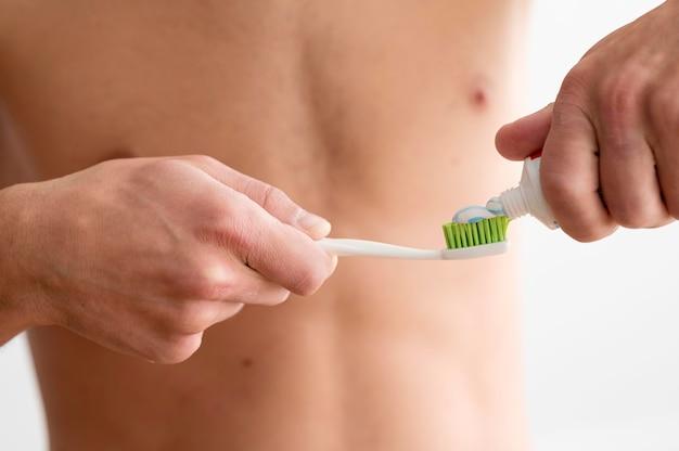 歯ブラシに歯磨き粉を塗る上半身裸の男の正面図 無料写真