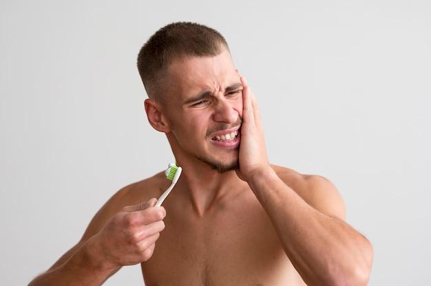 歯痛と歯ブラシを保持している上半身裸の男の正面図 無料写真