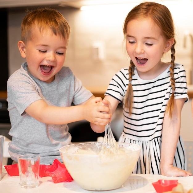 Вид спереди братьев и сестер, готовящих дома Бесплатные Фотографии