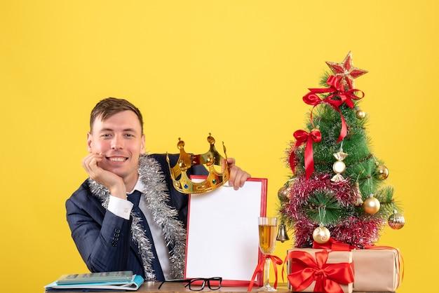 クリスマスツリーの近くのテーブルに座って、黄色でプレゼント笑顔のハンサムな男の正面図 無料写真