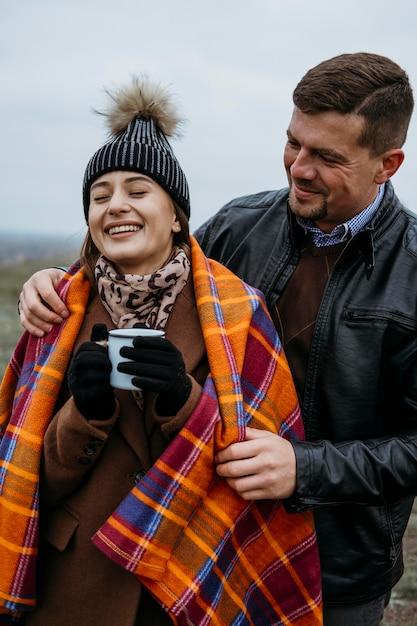 Вид спереди смайлик пара на открытом воздухе с одеялом и теплым напитком Бесплатные Фотографии