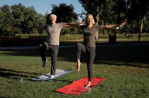 Вид спереди пожилой пары смайликов, практикующих йогу на открытом воздухе Premium Фотографии