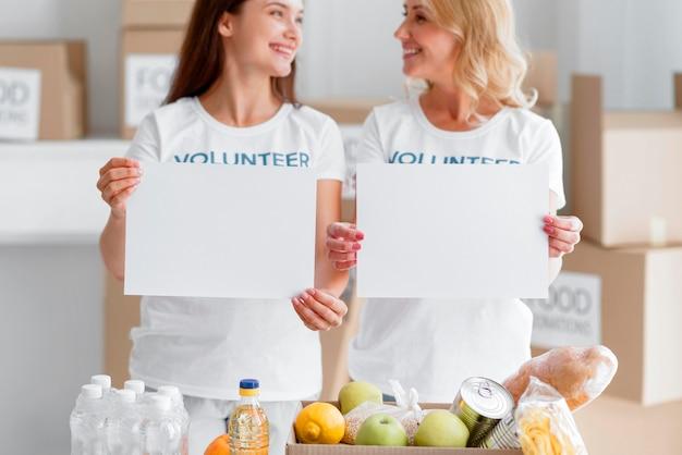 Вид спереди смайликов-добровольцев-женщин, позирующих с пустыми плакатами и пожертвованными на еду Бесплатные Фотографии