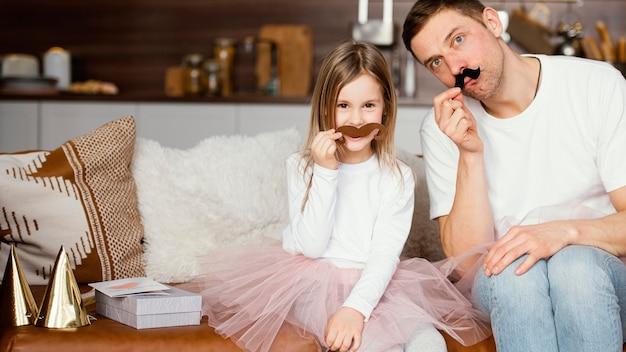 チュチュスカートのスマイリーガールと偽の口ひげを持つ父親の正面図 無料写真