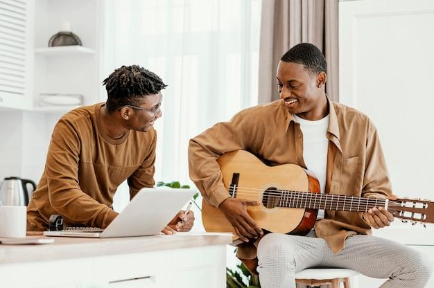 Вид спереди смайлика-музыканта дома на стуле, играющего на гитаре и использующего ноутбук Бесплатные Фотографии