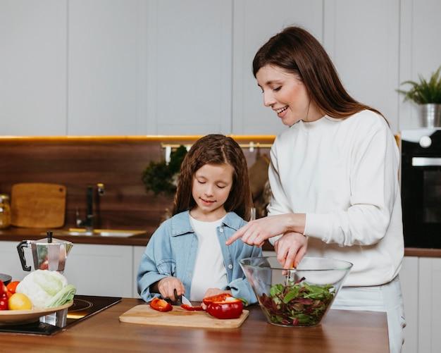 キッチンで食事を準備する笑顔の母と娘の正面図 無料写真