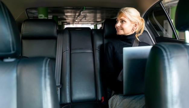 車のラップトップに取り組んでスマイリー古いビジネス女性の正面図 無料写真