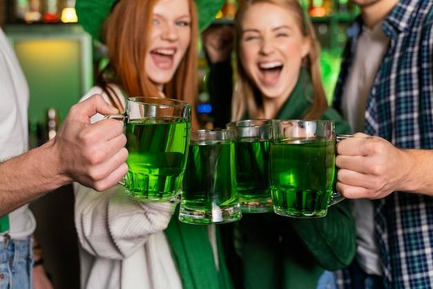 聖を祝う笑顔の人々の正面図。バーでのパトリックの日 無料写真