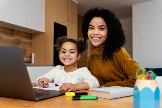 태블릿 온라인 학교 동안 여동생을 돕는 웃는 십 대 소녀의 전면보기 무료 사진