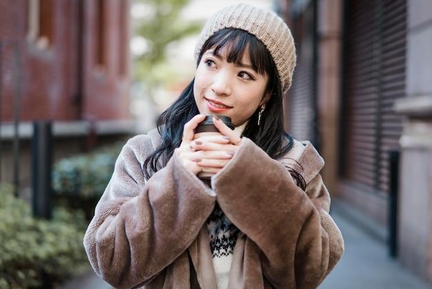 Вид спереди смайлика женщины с кофе на открытом воздухе Premium Фотографии