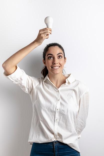 Вид спереди смайлик женщина держит лампочку Бесплатные Фотографии