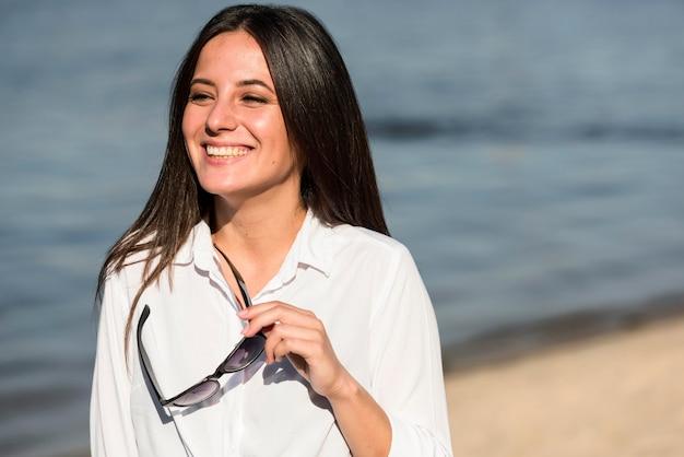 Вид спереди улыбающейся женщины на пляже, держащей солнцезащитные очки Бесплатные Фотографии