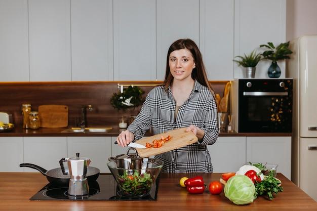 キッチンで食事を準備する笑顔の女性の正面図 無料写真