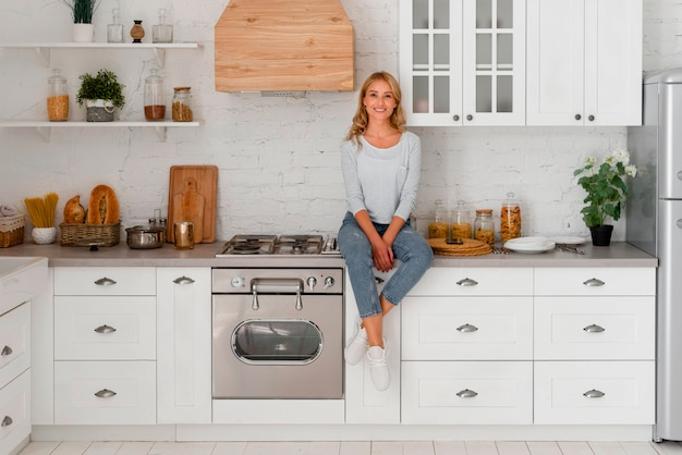 台所に立っている笑顔の女性の正面図 Premium写真