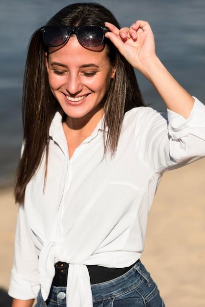 Вид спереди смайлика женщины с очками на пляже Бесплатные Фотографии
