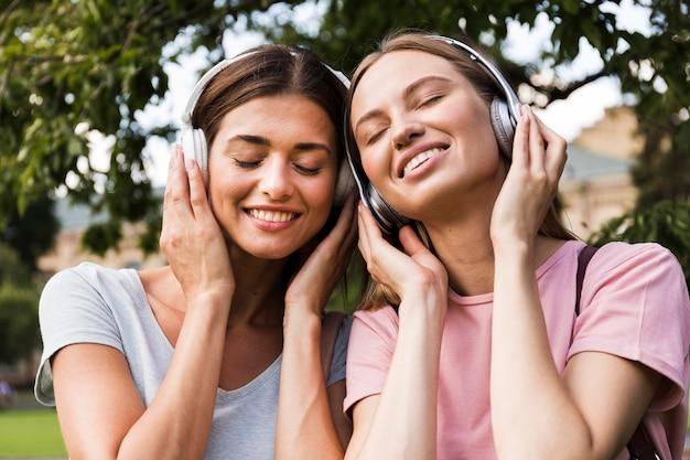 Вид спереди улыбающихся женщин на открытом воздухе, слушающих музыку в наушниках Бесплатные Фотографии