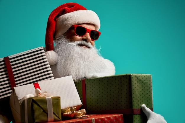 엄지 손가락을 나타나는 흰 수염과 산타 클로스 미소의 전면 모습. 크리스마스 의상 및 안경 포즈 잘 생긴 수석 남자의 고립 된 초상화 휴일의 개념입니다. 무료 사진