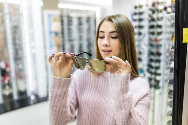 Вид спереди улыбающейся женщины в белом свитере попробовать очки в профессиональном магазине на Бесплатные Фотографии