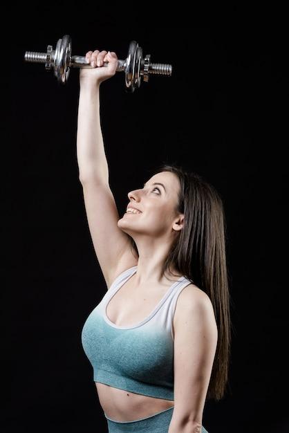Вид спереди спортивной женщины с гантелями Бесплатные Фотографии