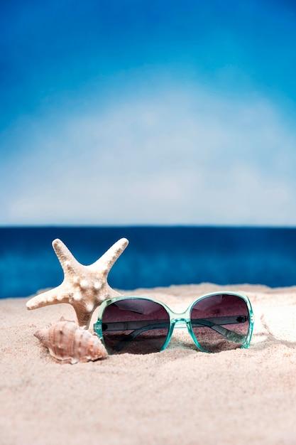 ビーチでのサングラスとヒトデの正面図 Premium写真