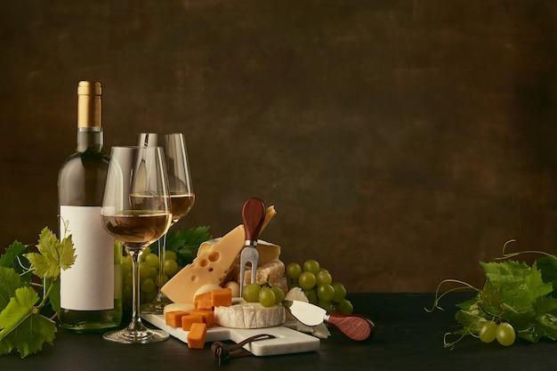 포도와 와인 병, 과일 및 와인 잔과 함께 맛있는 치즈 플레이트의 전면보기 무료 사진